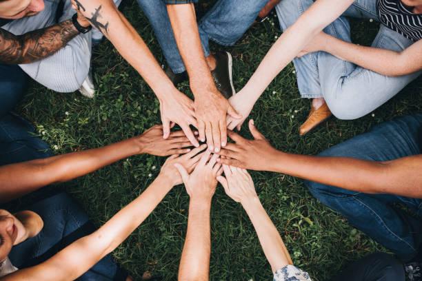 pessoas empilhamento mãos juntos no parque - apoio - fotografias e filmes do acervo