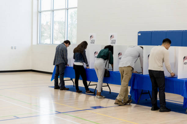 People stand at voting booths along the gym wall stock photo