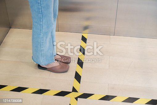 People stand on designated areas to ensure social distancing inside an elevator. COVID-19 Pandemic Coronavirus.