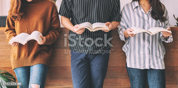 Three young people standing and enjoyed reading books together
