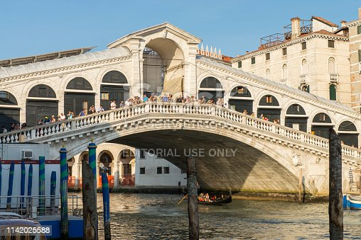 People standing and walking on the Rialto Bridge over the Grand Canal at Venice, Italy. The Grand Canal is an ancient waterway that goes from the Saint Mark Basin to a lagoon near the Santa Lucia rail station and is lined with buildings constructed from the 13th to the 18th centuries by wealthy Venetian families. The Rialto bridge is considered the most beautiful and famous of the four bridges that cross the Grand Canal. The gondola tour is a prefered attraction for the tourist at Venice.