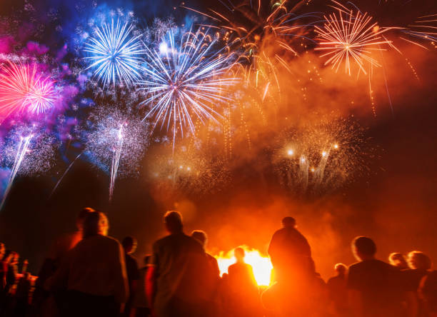 people standing in front of colorful firework - fireworks stock pictures, royalty-free photos & images