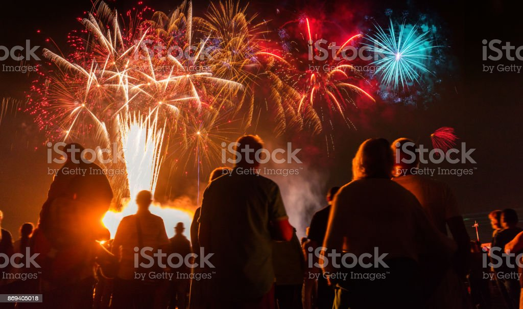People standing  in front of colorful Firework stock photo
