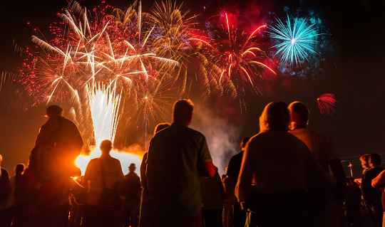 People Standing In Front Of Colorful Firework Stock Photo - Download Image Now