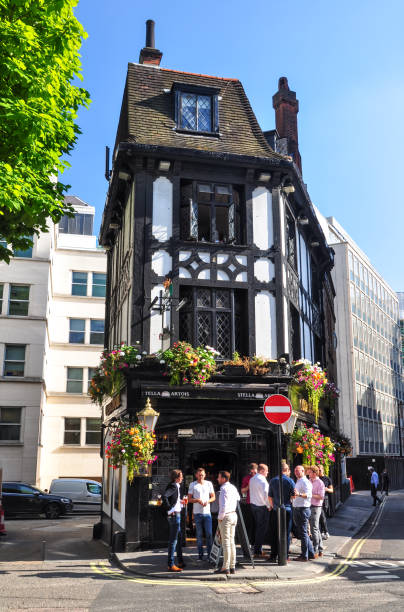 People standing in front of the Coach and Horses pub in Bruton Street, Mayfair, London, UK. The Coach and Horses is one of the best-known British pub names. London, UK - August 17, 2016: People standing in front of the Coach and Horses pub in Bruton Street, Mayfair, London, UK. The Coach and Horses is one of the best-known British pub names. mayfair stock pictures, royalty-free photos & images