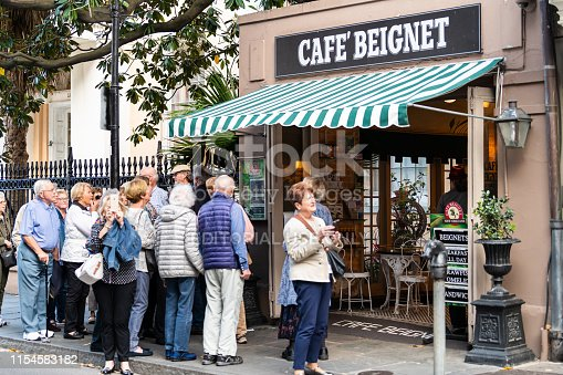 New Orleans, USA - April 23, 2018: People standing in line queue during day for famous restaurant cafe beignet powdered sugar donuts