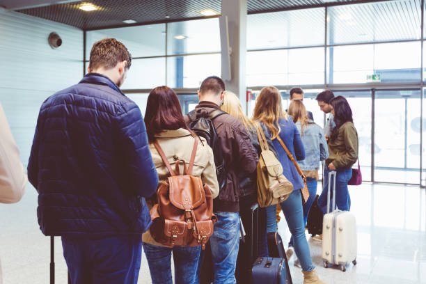 People standing in queue to board plane stock photo