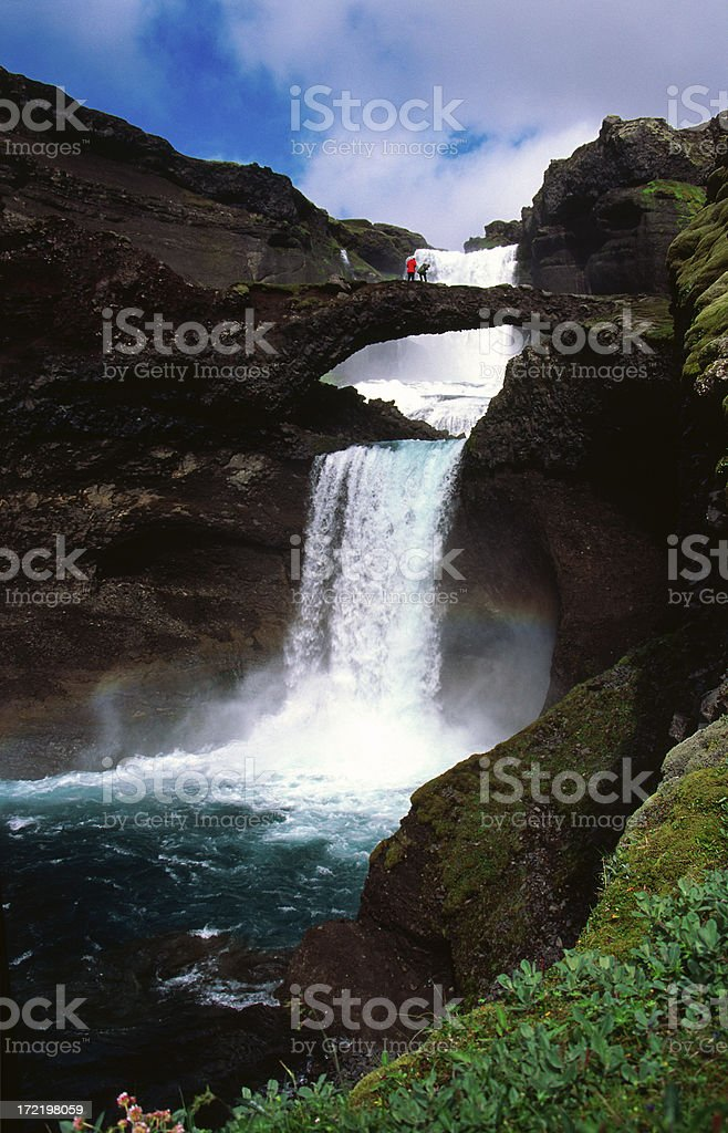 People standing on natural bridge over Ofaerufoss stock photo