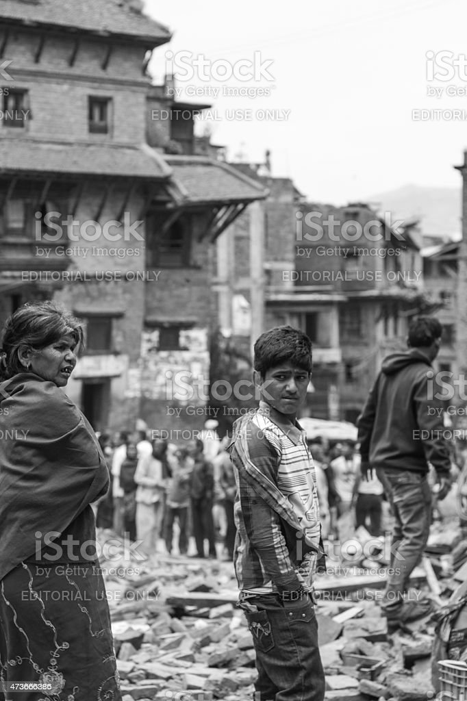 people standing on the ruins of the collapsed building stock photo