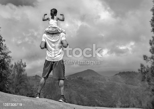 Black and white photo of a kid making a muscle pose riding on her fathers shoulders