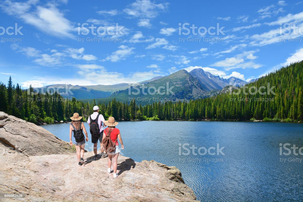People standing on top of mountain  looking at beautiful landscape. stock photo