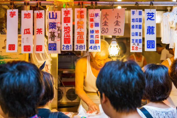 People standing outside a famous dumpling shop Taiwanese people standing outside a famous dumpling shop in Jiufen old town on August 17, 2014 in Jiufen night market stock pictures, royalty-free photos & images