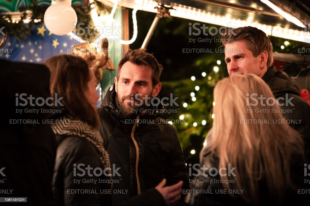 People standing together and talking outside a market stall at a Christmas street market. stock photo