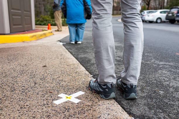 People standing waiting in line far apart to maintain social distance distancing during covid-19 coronavirus outbreak with mark cross signs on sidewalk pavement by grocery food store shop shopping stock photo