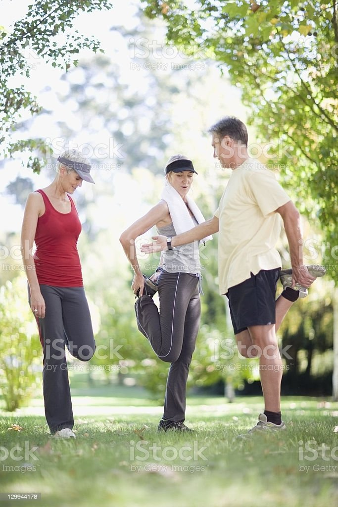 People stretching together outdoors stock photo