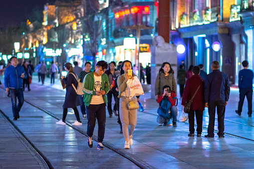 Beijing / China - April 7, 2016: People stroll along the historic Qianmen Street south from Tiananmen Square in Beijing, at night