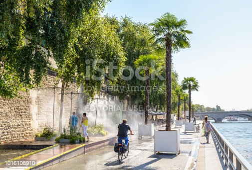 istock People strolling and biking between palm trees on the banks of the Seine in Paris, France, during Paris-Plage summer event while other cool themselves down under water misters. 1016108910