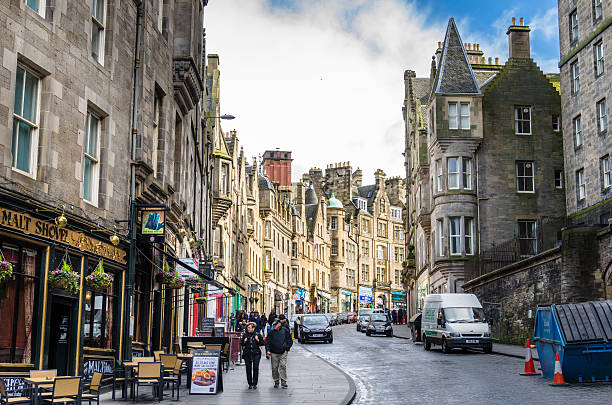 People Strolling around Edinburgh's City Centre Edinburg, UK - March 28, 2015: Locals and Tourists Strolling along Cockburn Street in Old Town on a cloudy winter day. Cockburn Street is a picturesque street created as a serpentine link from the Royal Mile to Waverley Station in 1856 in Edinburgh's city centre. edinburgh scotland stock pictures, royalty-free photos & images