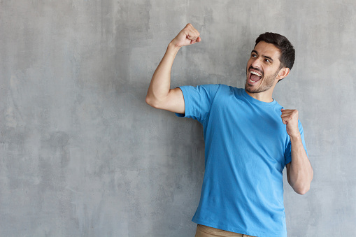 istock People, success, winning and celebration concept. Young successful man screaming yes and raising clenched fist, copy space for your text 1029759456