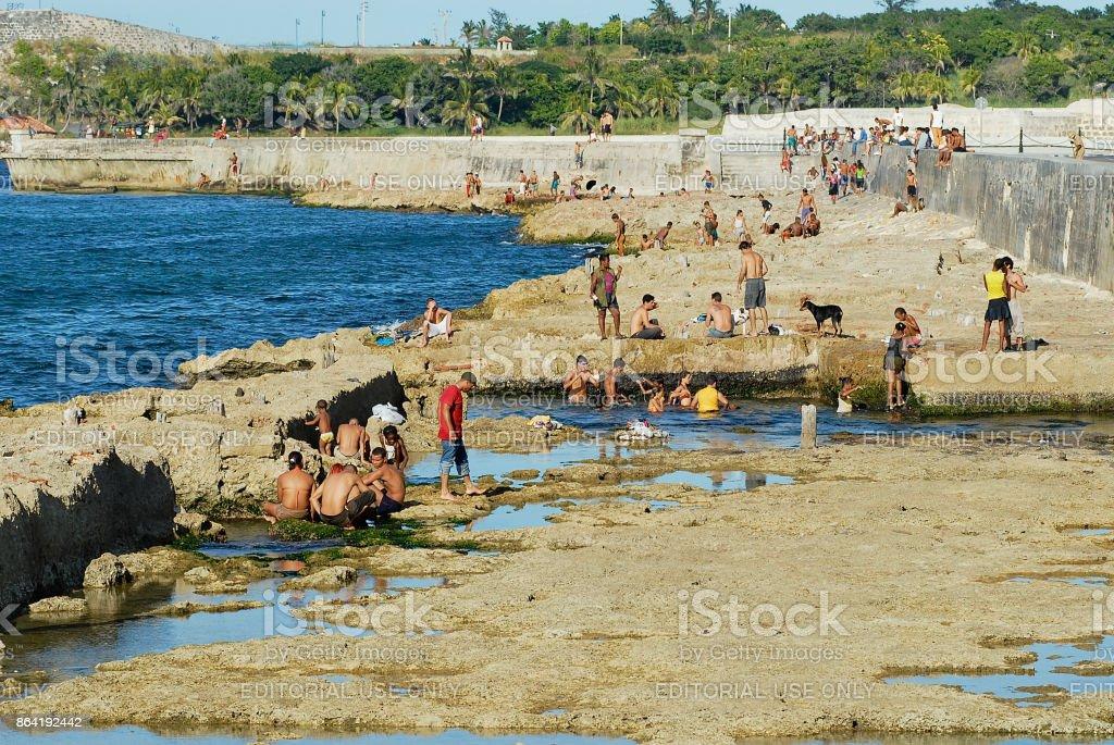 People sunbathe at the Malecon seawall in Havana, Cuba. royalty-free stock photo