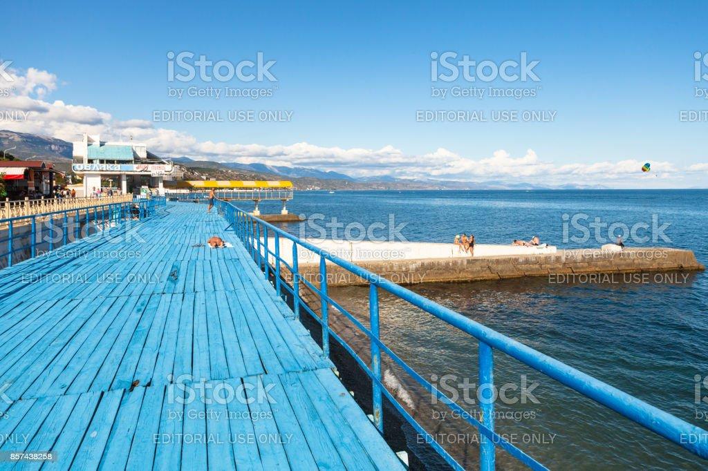 people sunbathe on wood solarium in Alushta stock photo