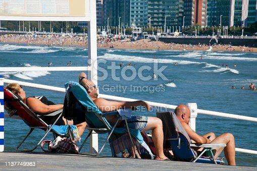 Gijon, Spain-August 31, 2018: Side view of three people sunbathing on the sidewalk, looking at view of cityscape of San Lorenzo beach in Gijón, Asturias, Spain, seen from the street.  Incidental people in the beach, sea,cityscape in the background.