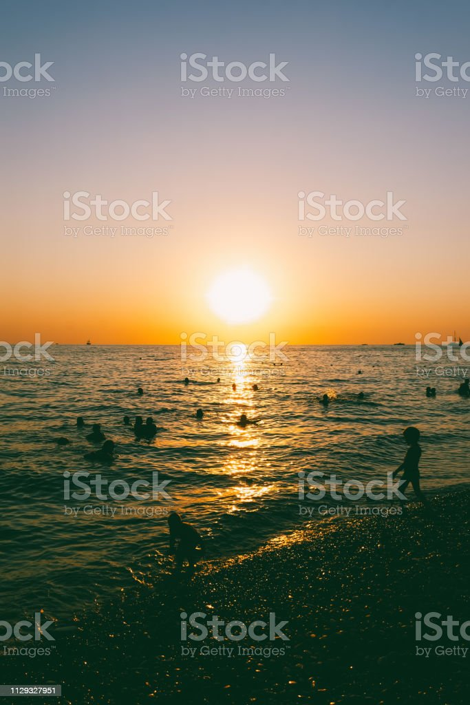 people swim in the sea in the evening at sunset