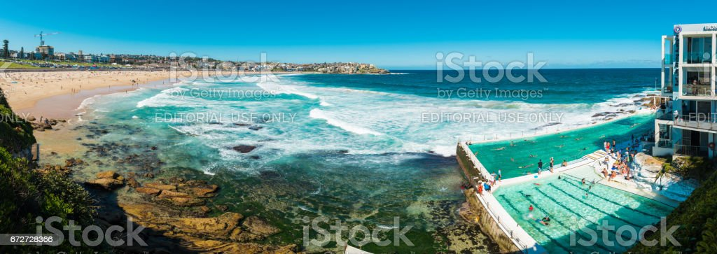 People swimming in the fresh water swimming pools built in to the sea with waves rolling in to Bondi and breaking against the edge of the pool stock photo