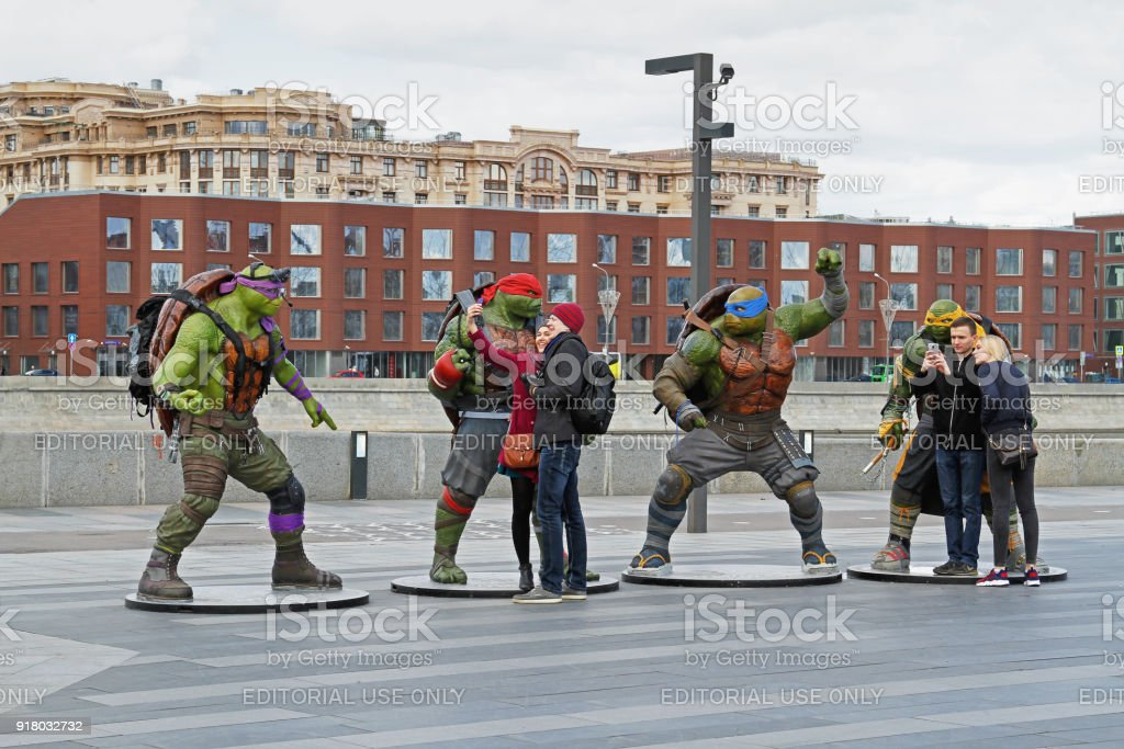 People take a selfie with phone on a background of teenage mutant ninja turtles figures in the park Muzeon in Moscow stock photo