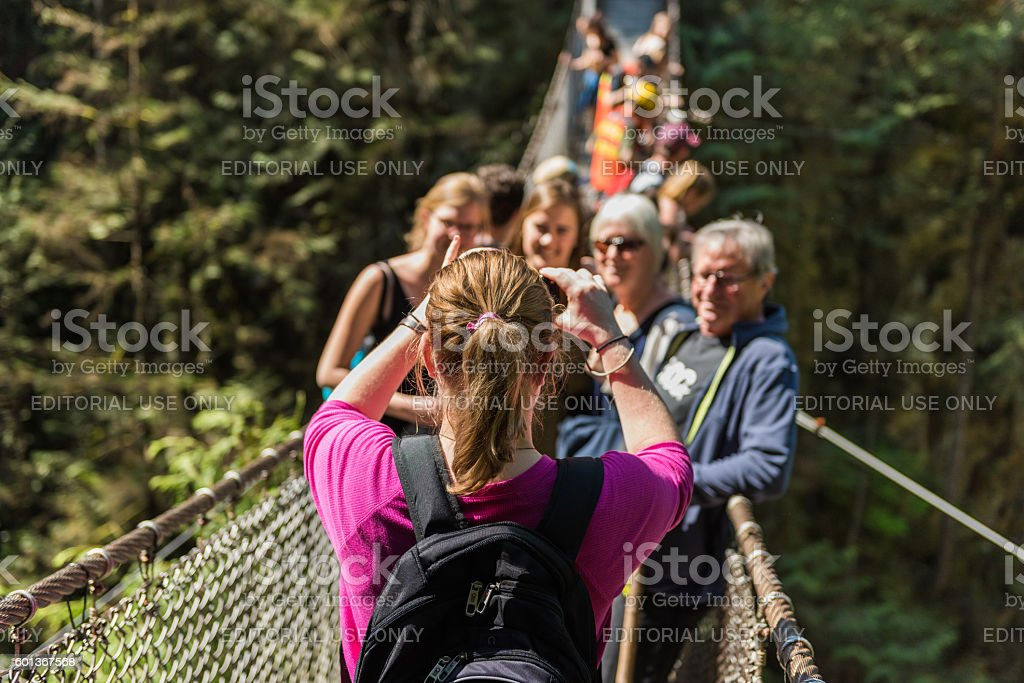 People taking a group photo on Lynn Canyon Suspension Bridge stock photo