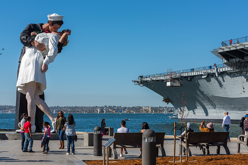 People taking a selfie at sailor and nurse while kissing statue san diego
