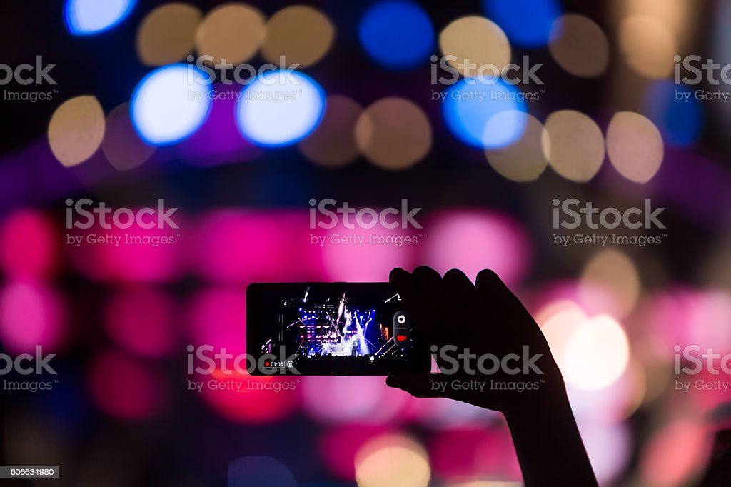 People taking photographs with touch smart phone during a music stock photo