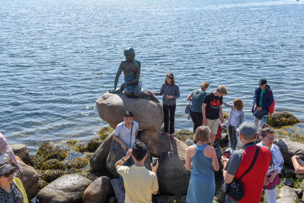 People taking pictures with the Sirenetta statue at Copenhagen on Denmark stock photo