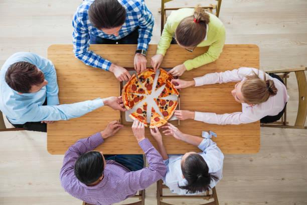 Menschen, die Pizza-Scheiben nehmen – Foto