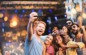 Group of friends taking selfie in front of a stage at music festival.