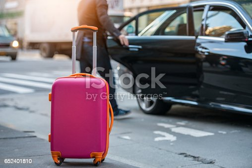 istock People taking taxi from an airport loading carry-on luggage bag 652401810