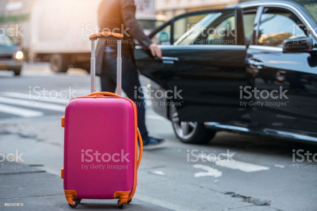 People taking taxi from an airport loading carry-on luggage bag stock photo