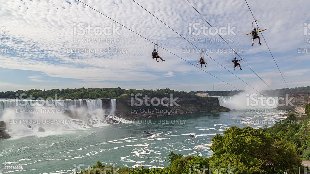4 people taking zipline ride, Niagara Falls, Ontario. stock photo