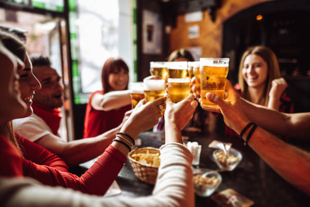люди говорят и тосты в пабе с пивом - напиток стоковые фото и изображения