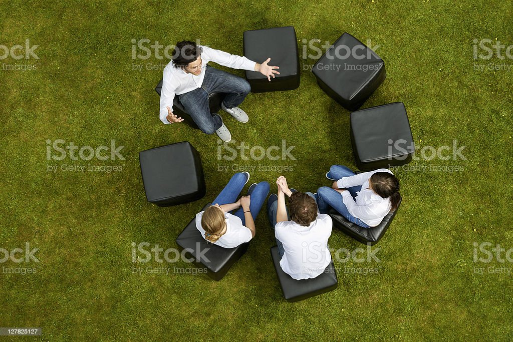 People talking in circle in grass royalty-free stock photo