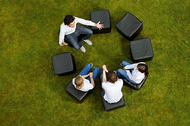 personnes discutant en cercle en herbe - persuasion photos et images de collection