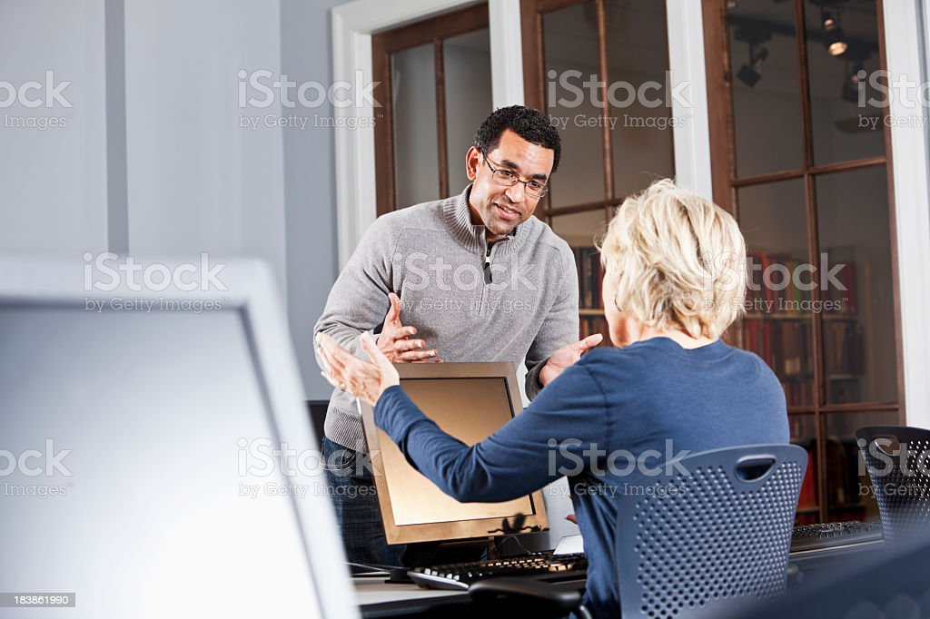 People talking in computer lab stock photo