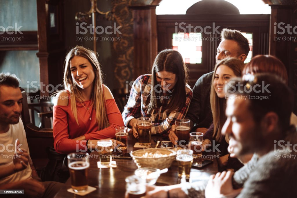 people talking indoors in a pub with the beers stock photo