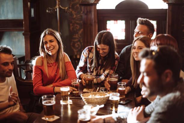 pessoas falando dentro de casa em um pub com as cervejas - foto de acervo