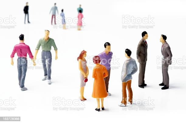 A group of model people dressed brightly, chatting amongst themselves on a white backdrop