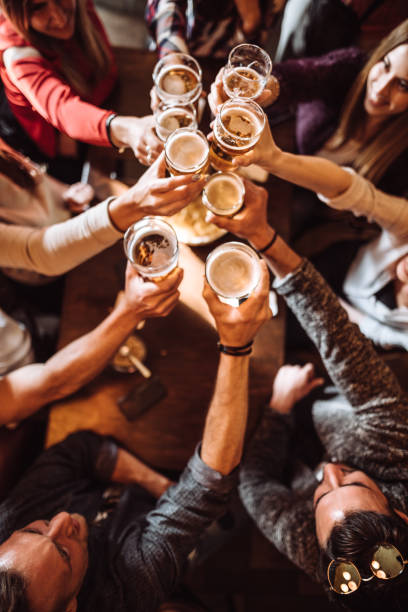 people talking toasting in a pub with the beers stock photo