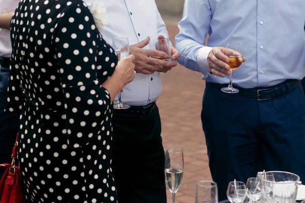 menschen toasten bei luxus-hochzeitszeremonie empfang. braut und stilvolle bräutigam mit familiengästen toasten jubeln mit champagner-gläser - outdoor braut duschen stock-fotos und bilder