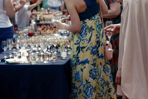menschen toasten bei hochzeitszeremonie empfang. gäste mit champagnergläsern. offene bar im park, familie und freunde jubeln mit getränken - outdoor braut duschen stock-fotos und bilder
