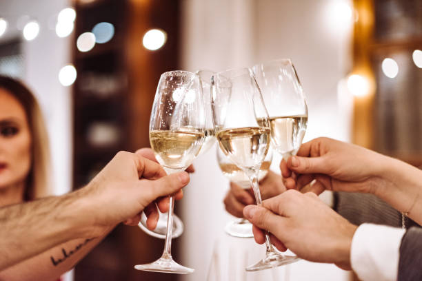 people toasting champagne at dinner stock photo