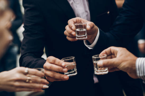 people toasting holding glasses of vodka cheering at wedding reception, celebration outdoors, catering in restaurant. christmas and new year people toasting holding glasses of vodka cheering at wedding reception, celebration outdoors, catering in restaurant. christmas and new year vodka stock pictures, royalty-free photos & images